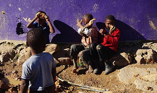 African boys playing by a blue painted wall