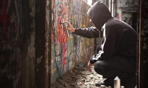 Young male applying spray paint to a wall, graffiti